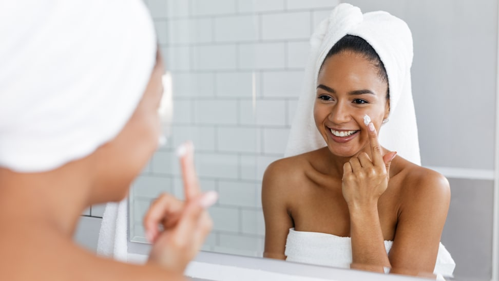 A person standing in front of a large bathroom mirror applying a moisturizer to her face while wearing a towel around her body and hair.