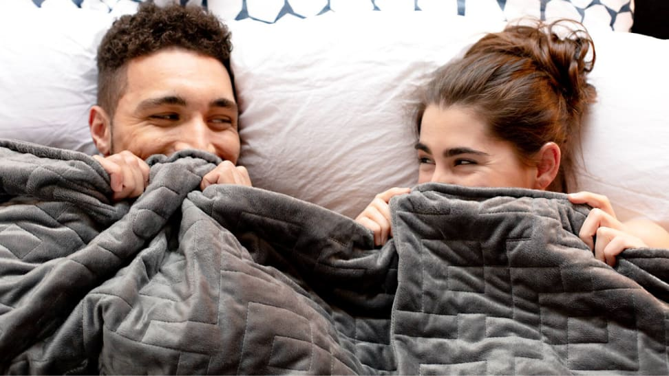 Couple giggling under a weighted blanket