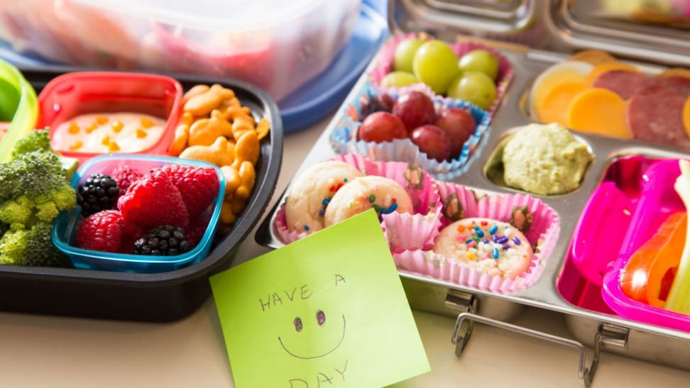 Colorful school lunches in bento boxes with a smiley note.
