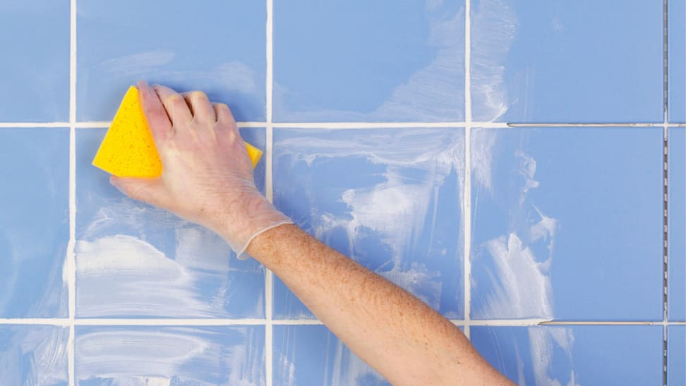 A hand wearing a glove washes a tiled wall with a sponge.