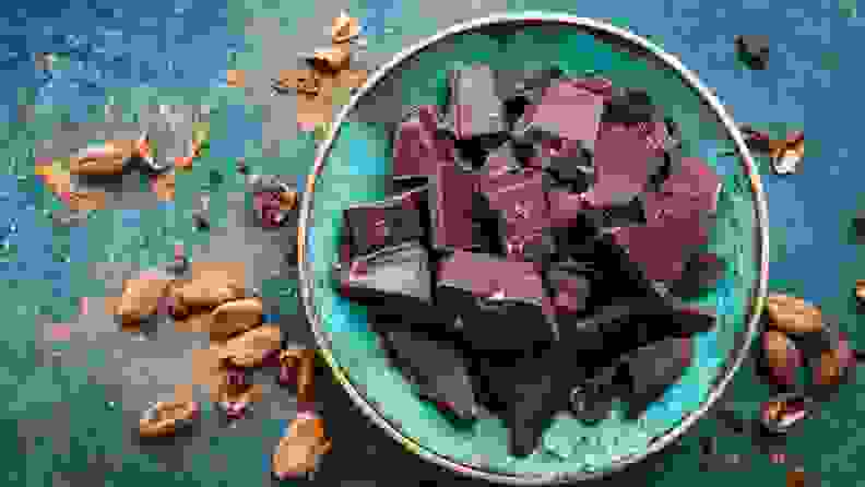 a bowl of dark chocolate surrounded in powder and on a teal background