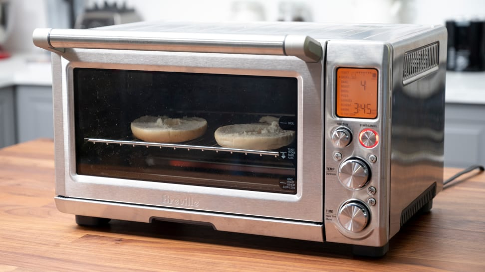 A Breville Smart Oven Pro on a kitchen counter with a bagel toasting inside.