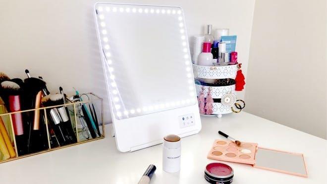 The Glamcor Riki Skinny Makeup Mirror on a white desk.