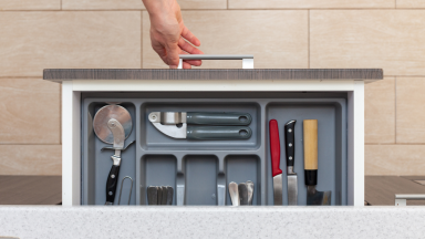 A drawer of kitchen utensils being opened.