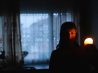 Person standing in dark room with a window behind them, holding a lit candle up to face