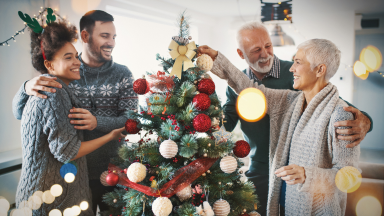 Four people decorate a Christmas tree with ornaments.
