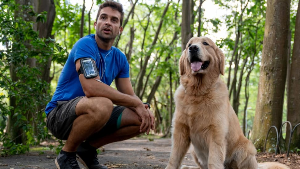 A runner bends down next to their dog on a wooded running path