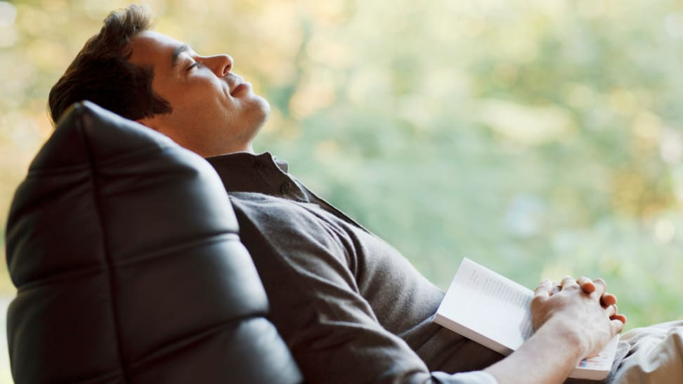 A person naps in a chair with a book.