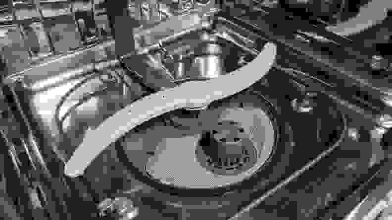 A shot of the bottom of the GE GDP645SYN0FS dishwasher's interior. We can see its spray arm and a large, clearly labeled filter.