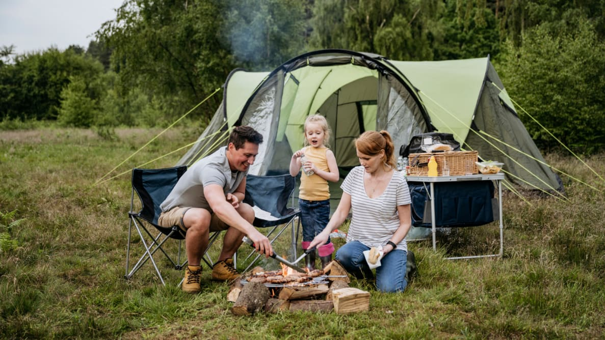 Family grills in front of a tent.
