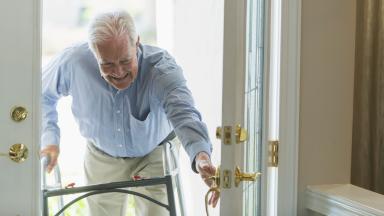 An elderly person utilizing a walker opens a house door.