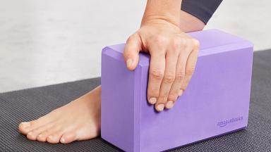 A yoga practitioner balances on a foam yoga block.