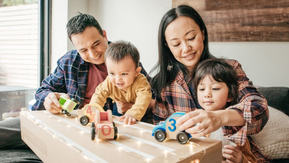 Family playing with toy cars in a living room.