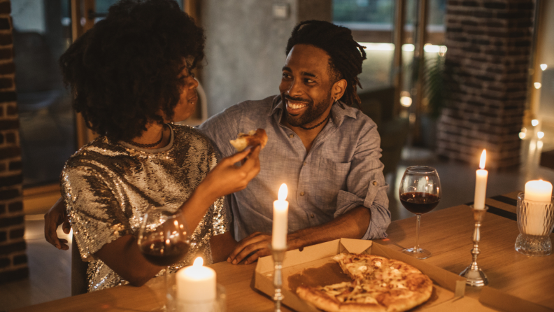 A smiling couple shares a pizza and wine by candlelight.