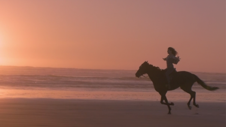 A still from Black Beauty featuring the horse and Jo riding together on the beach.