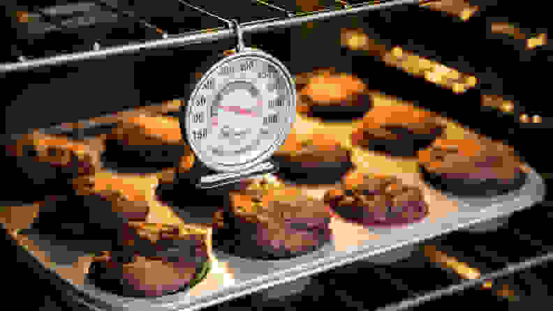 An oven thermometer hanging in front of a tray of muffins.