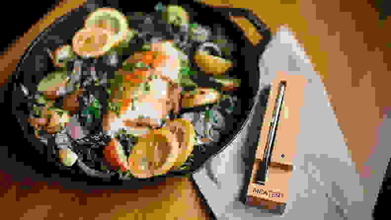 A fish dish in a cast iron pan beside the Meater Plus thermometer.
