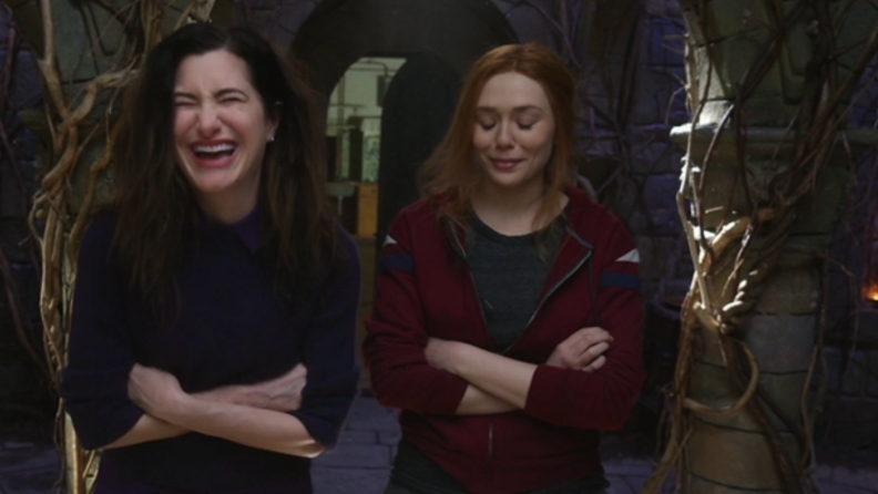A still from the Assembled series featuring Kathryn Hahn and Elizabeth Olsen in costume, breaking character by laughing.