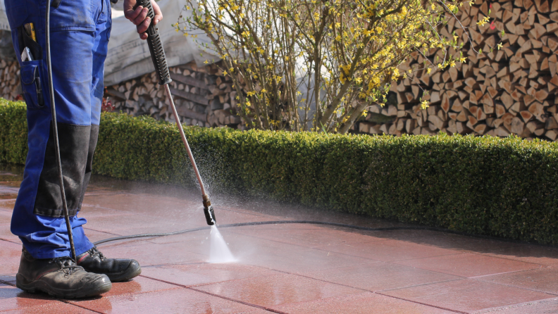Person spraying down tile surface around yard