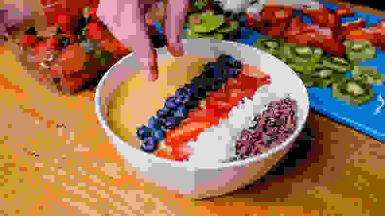 Adding blueberries to smoothie bowl