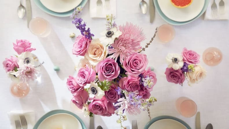 An aerial shot of a bouquet of purple and pink roses, as the centerpiece on a table covered in white linen and dainty white china plates.