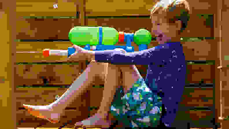 A boy shoots a Nerf Super Soaker