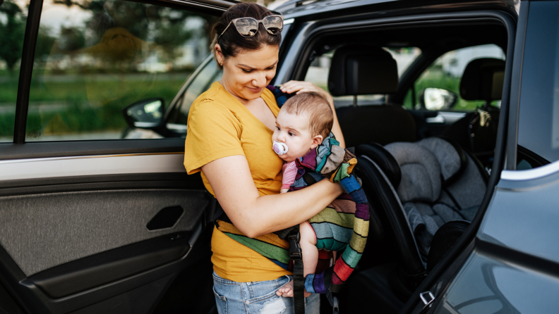 Person holding baby next to car seat.