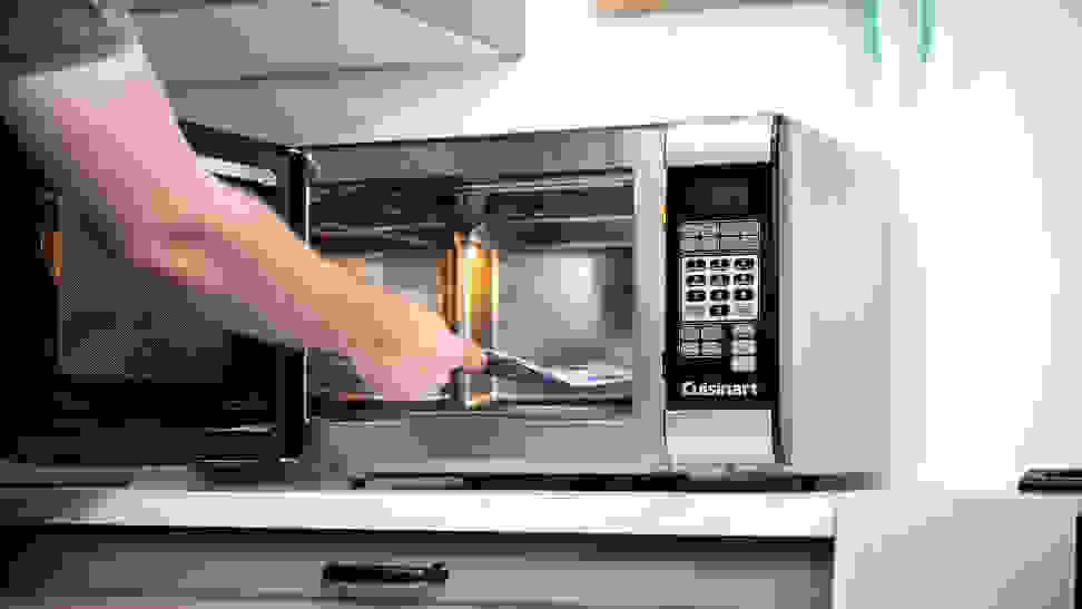 Placing a popcorn bag in a microwave