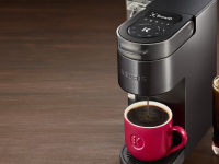 Against a brown backdrop, there's a black stainless steel Keurig single serve pod coffee maker brewing coffee. Next to the machine, there's a glass of iced coffee.