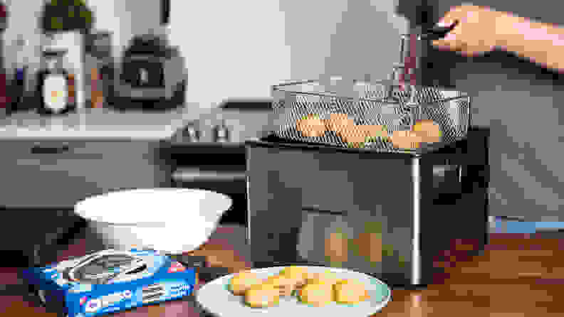 The Hamilton Beach Professional Grade Deep Fryer filled with fried food sits on a kitchen counter.