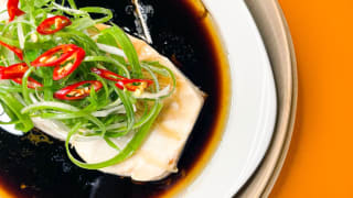 A white plate with steamed white fish topped with soy sauce, green onions, whole ginger, and limes.