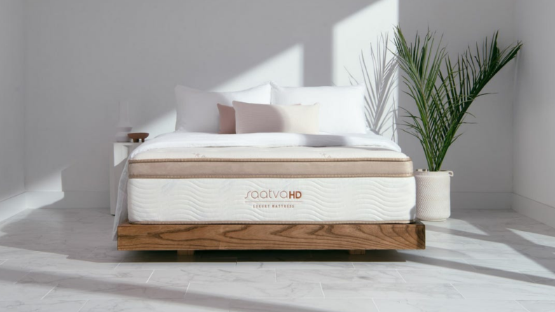 A Saatva mattress inside a minimalistic bedroom.