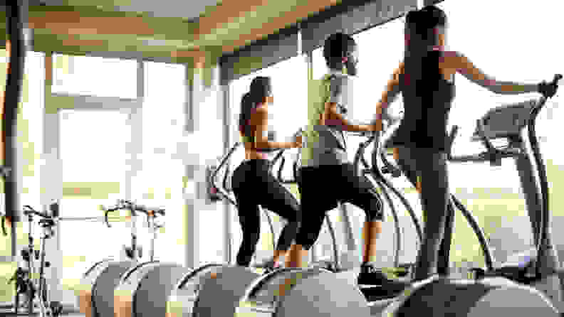 Three people using elliptical machines at the gym.