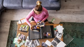 A person adds photos to a photo album at home.