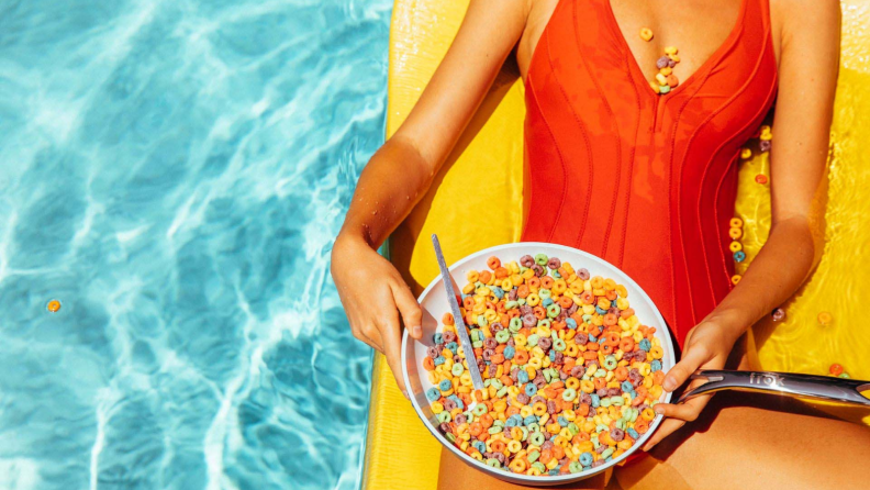 A bathing suit-wearing person, who's sitting on a yellow float in a pool, is holding and potentially eating cereal from a Frök frying pan.