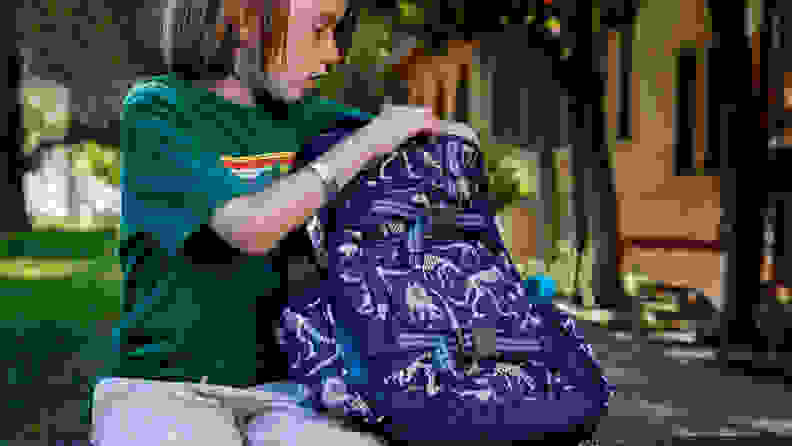 A young boy sitting on a bench putting books in a backpack