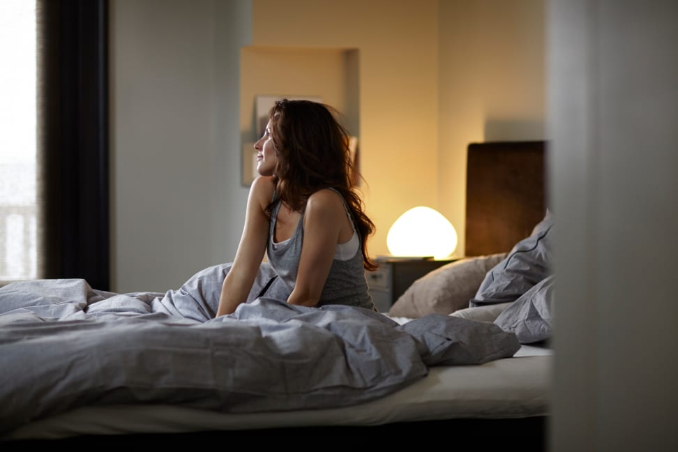 A woman wakes up with a Philips Hue White Ambiance bulb in a lamp in the background