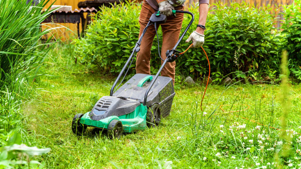 A person pushing a lawnmower mowing a lawn