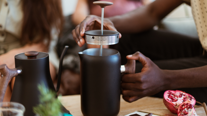 A person is lifting the lid from a Fellow Clara French press in a living room.