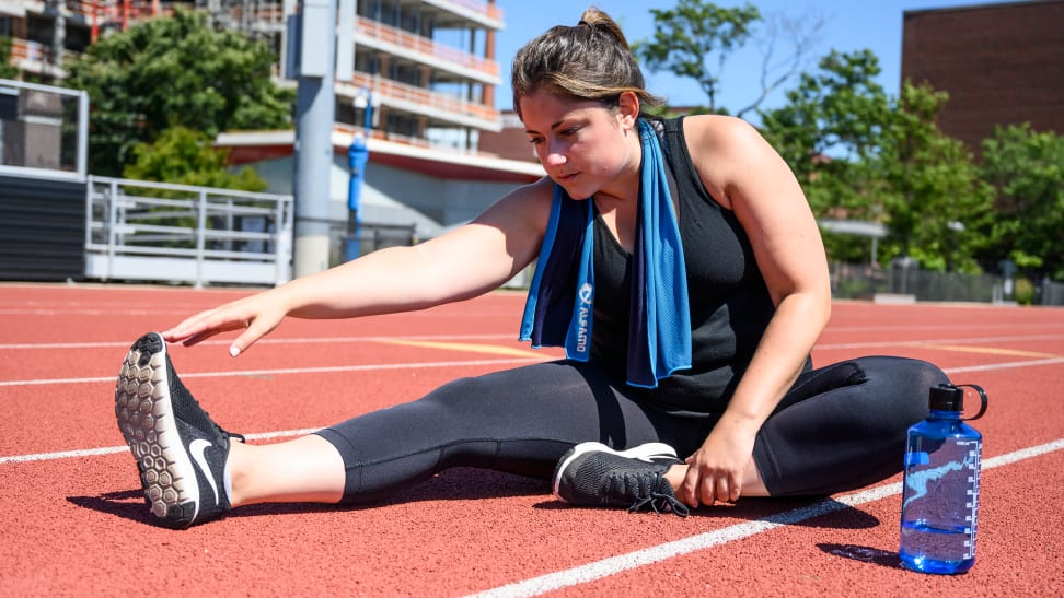 Woman runner stretching on a track