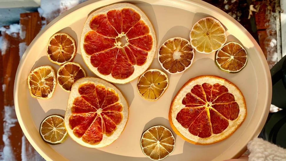 There are 12 pieces of dehydrated citrus slices on a plate, including grapefruit, lemon, and lime.