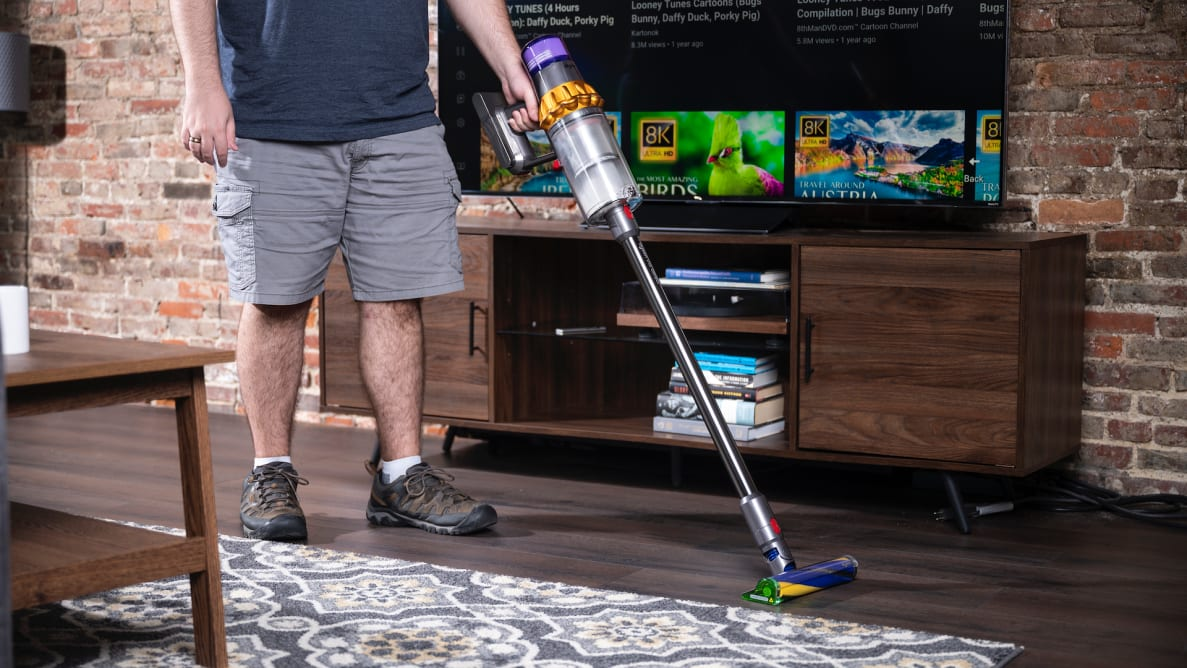 A person uses a Dyson V15 vacuum to clean the fllor