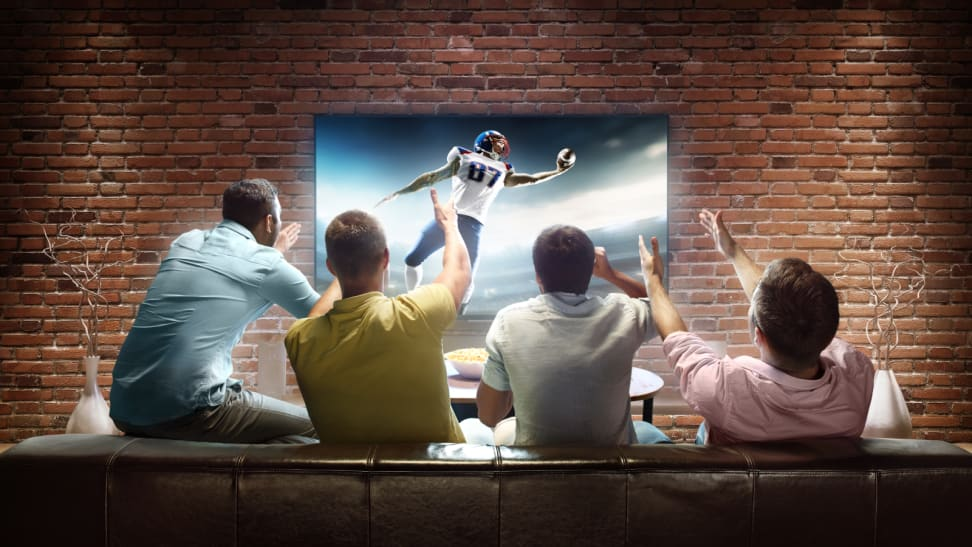 Four guys cheering in multi-colored shirts while watching football on a big-screen TV