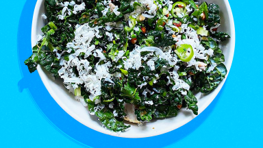 A kale salad topped with feta cheese, served in a white bowl and placed on a blue background.