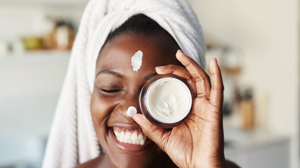 A woman wearing a towel on her head and smiling as she holds up a jar of cream in front of her eye. She has a strip of moisturizer on her forehead and on her nose.