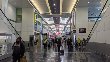 Masked people walk though an airport in 2021