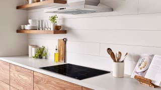 A lifestyle image of a brightly lit, modern kitchen featuring an induction cooktop.