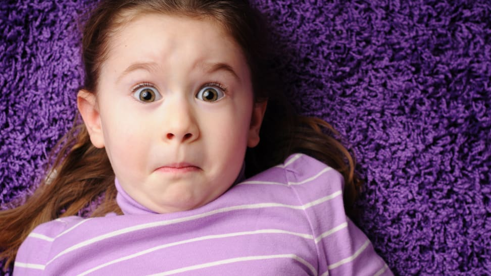 Girl with surprised face laying on purple carpet