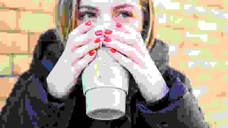 A photo of a woman sipping from the Stojo Cup.