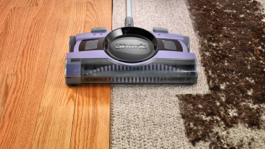 Close-up photo of the Shark V2950 Cordless Sweeper, which is lavender in color, as it cleans a dirty carpet.